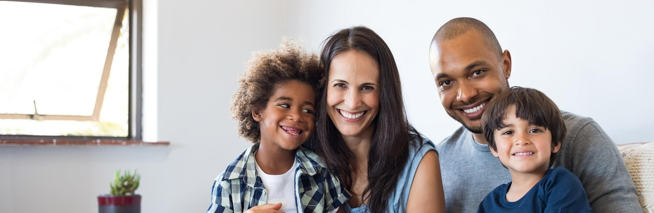 Multi-racial family holding drawing of happy family